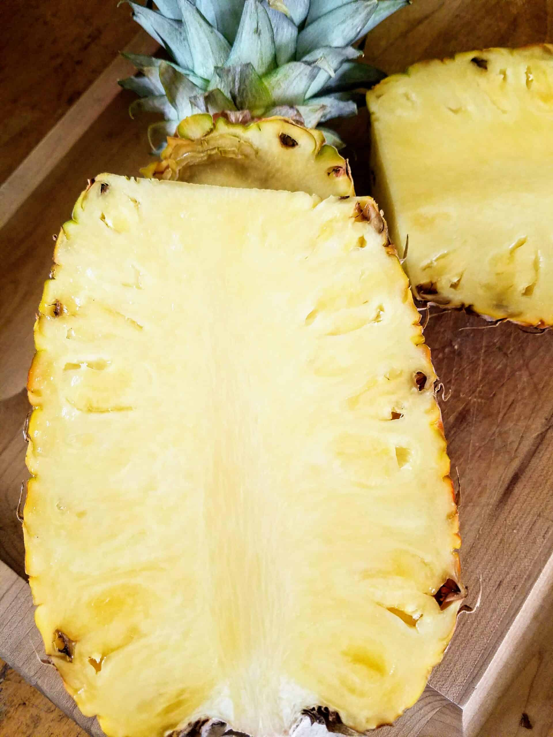 a half of a pineapple frshly cut on cutting board