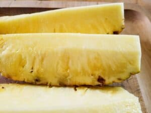 Pineapple ready to be peeled cut into spears