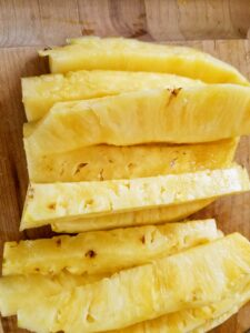 freshly cut pineapple slices on cutting board