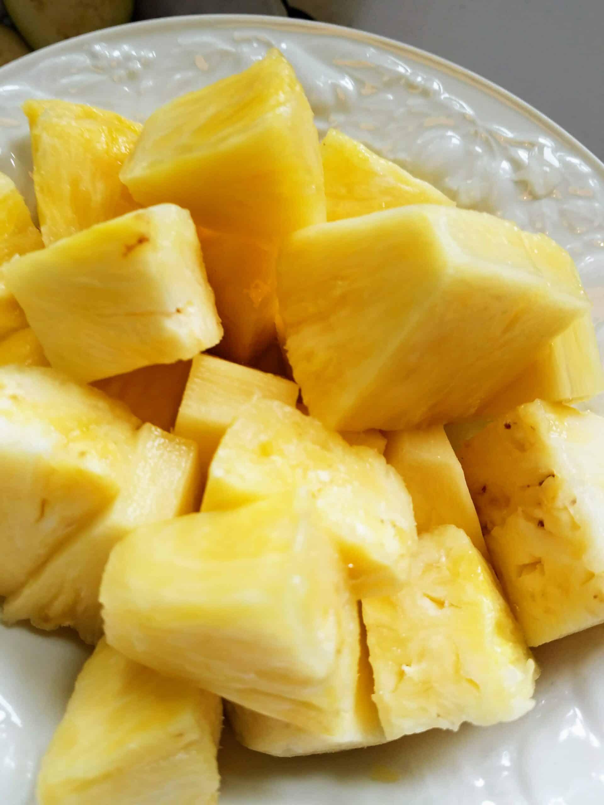 chunks freshly cut pineapple in a white bowl