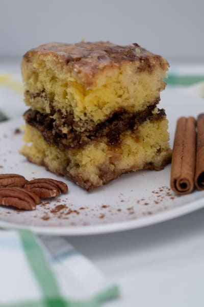 sliced honey bun cake plated with nuts and cinnamon sticks