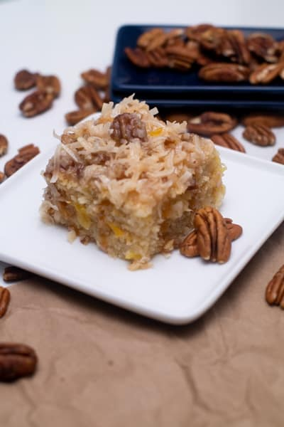coconut pecan pineapple cake on white plate serving