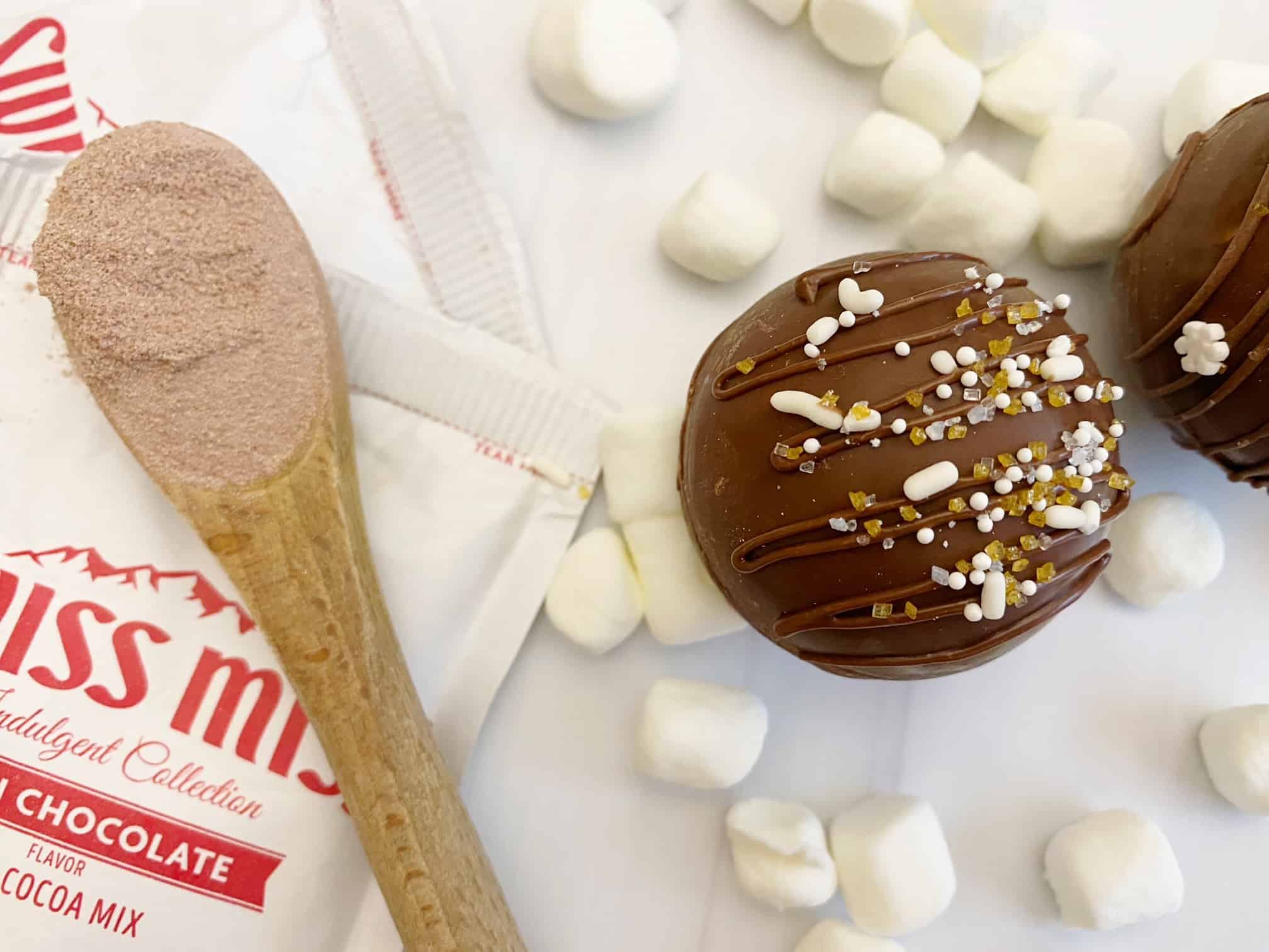 package swiss miss, wooden spoon, marshmallow, hot cocoa bomb